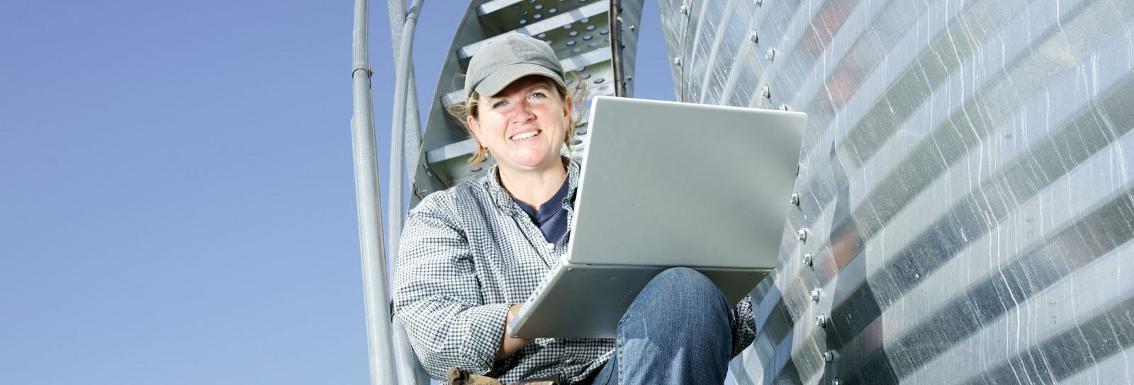 Farm safety coordinator sitting on a grain bin stairway, reviewing her compliance reports on a laptop.